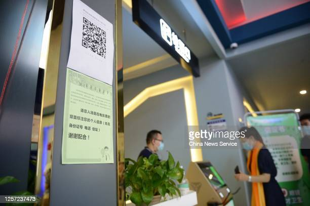 Moviegoers wearing masks line up to scan a health QR code before entering a screening hall at a cinema almost six months after its closure due to the...