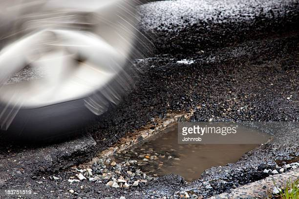 Moving auto tire about to enter large pothole, Motion blur