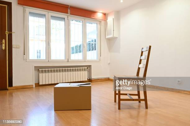 Moving box and chair in an empty room.