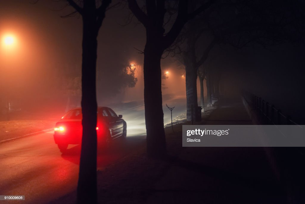 Moving car and walkway on misty night : Stock Photo