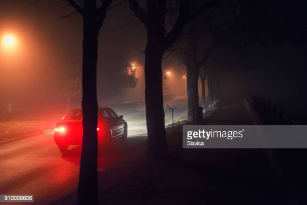 moving car and walkway on misty night - black alley stock photos and pictures