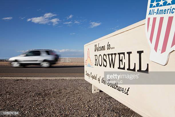 moving car driving past welcome to roswell sign - roswell stock pictures, royalty-free photos & images