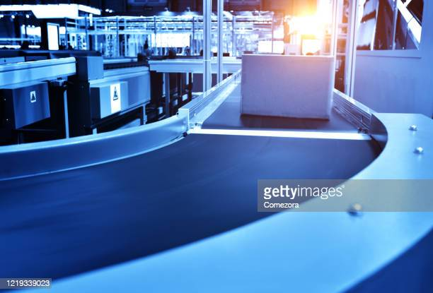 moving cardboard box on conveyor belt in distribution warehouse - conveyor belt stock pictures, royalty-free photos & images