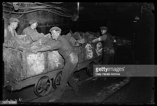 Moving coal in the Number 1 Pit in Powell Wales 1931 A photograph of miners hauling wagons at Number 1 Pit in Powell Wales taken by James Jarche for...