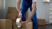 Moving company worker packing cardboard boxes, quality delivery services