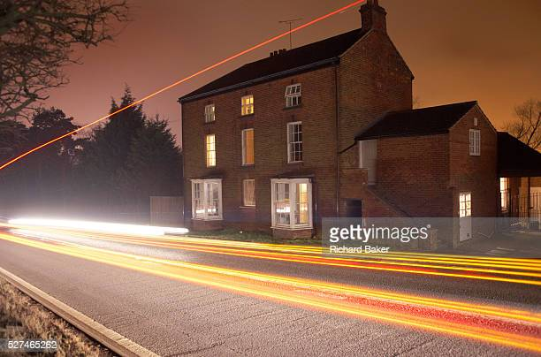 Moving fast past a farmhouse building on a busy UK A road unseen traffic leaves its light trails on an otherwise dark winter night near the giant...