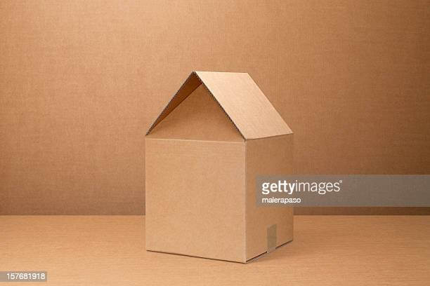 Moving home. Cardboard box shaped house.