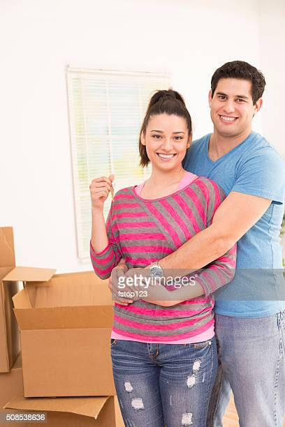Moving, Homes: Latin descent couple shows off key. New house.