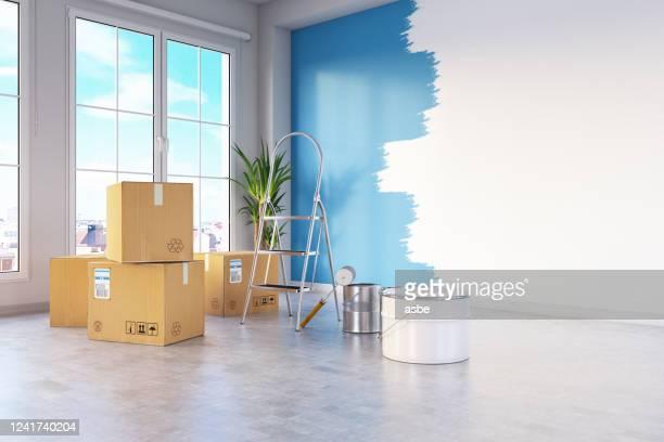umzughauskonzept mit kartons und wandmalerei - farbeimer stock-fotos und bilder