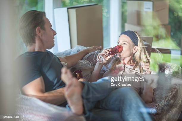 Moving house: couple relaxing on bubbled wrapped sofa, in room with cardboard boxes, drinking from champagne flutes