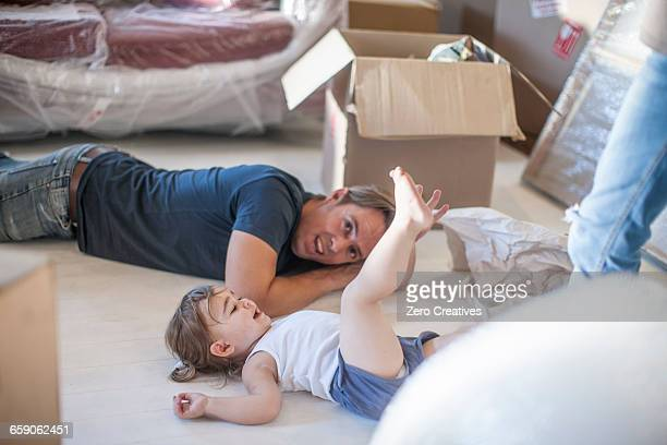 Moving house: father and daughter relaxing on floor of new home