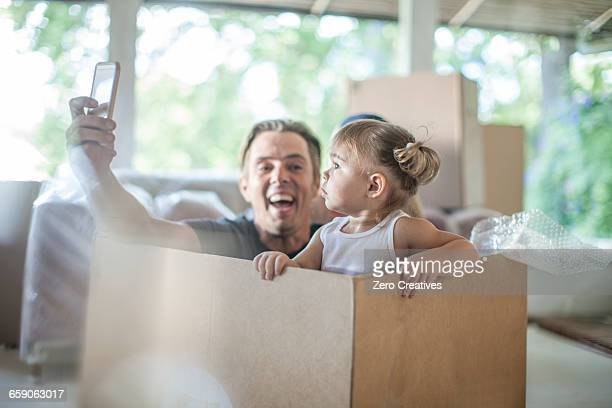 Moving house: father and daughter sitting in cardboard box, father taking self portrait using smartphone