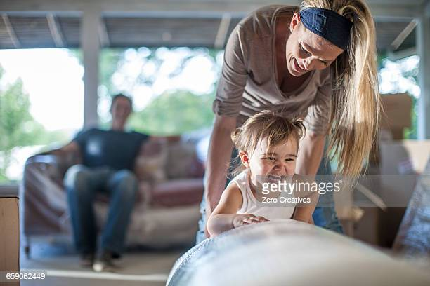 Moving house: man sitting on bubble wrapped sofa, woman playing with daughter