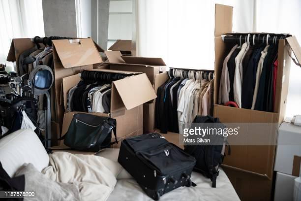 moving house with cardboard boxes and clothes and golf bag in living room - último cuarto deportes fotografías e imágenes de stock