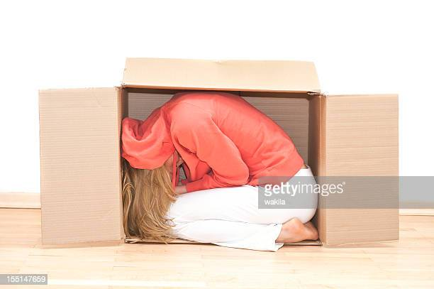 moving house - woman in cardboard frau im umzugskarton - claustrophobia stock photos and pictures