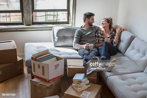 moving house: young couple relaxing on sofa surrounded by cardboard boxes - young couples stock pictures, royalty-free photos & images