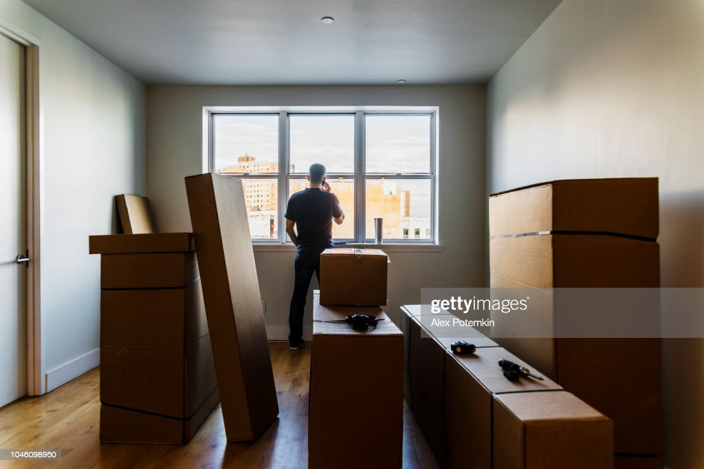Moving in! The mature Caucasian man talking by phone nearby the window in the empty living room filled with cardboard boxes, in the new house. : Stock Photo