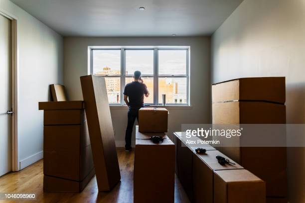 Moving in! The mature Caucasian man talking by phone nearby the window in the empty living room filled with cardboard boxes, in the new house.