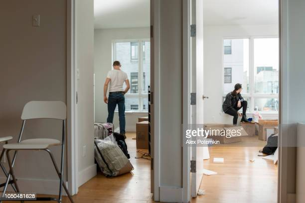 Moving into the new house. Teenage girl sitting in her future room between boxes with her stuff, and the young 28-years-old man looking around the apartment