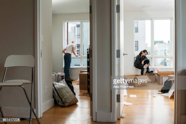 moving into the new house. teenage girl sitting in her future room between boxes with her stuff, and the young 28-years-old man looking around the apartment - 16 17 years stock pictures, royalty-free photos & images