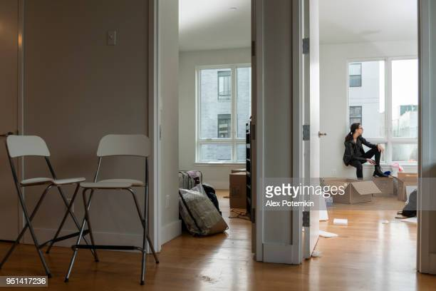 moving into the new house. teenage girl sitting in her future room between boxes with her stuff. - alex potemkin or krakozawr stock pictures, royalty-free photos & images