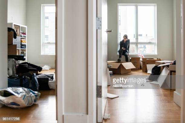 Umzug in das neue Haus. Teenager-Mädchen sitzt in ihrem zukünftigen Zimmer zwischen Kisten mit ihren Sachen.