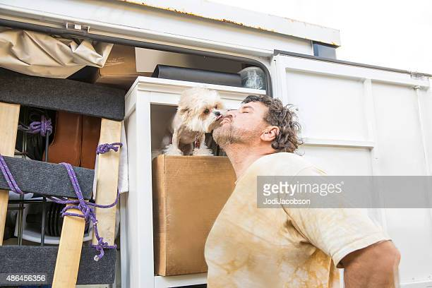 moving series: man gets kiss from dog inside  moving container - self storage stock pictures, royalty-free photos & images