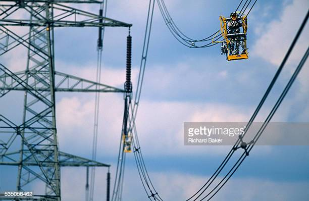 Moving steadily along a live-line electricity cable, a National Grid maintenance worker protected in a conductive cage, proceeds to the next...