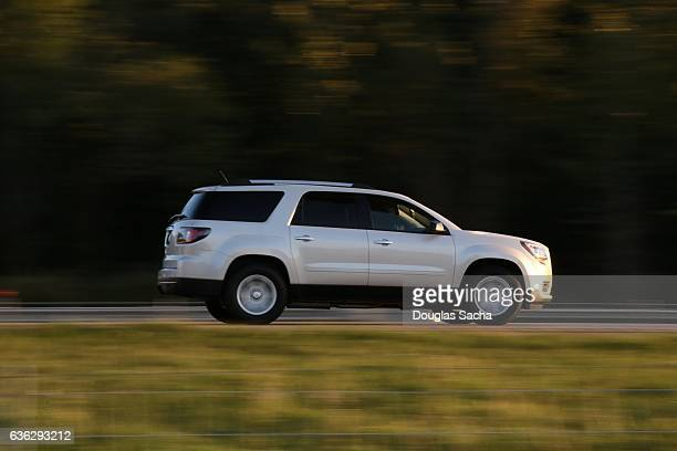 moving suv on a rural highway - seitenansicht stock-fotos und bilder