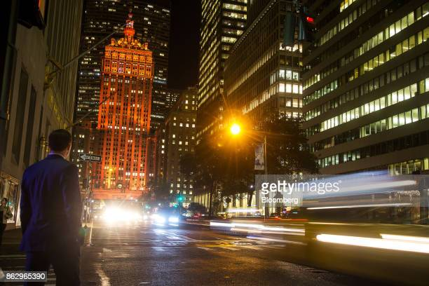 Moving traffic creates light trails as The Helmsley Building stands lit in orange to support a bid for Amazoncom Inc's second headquarters in New...