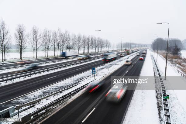moving traffic on a highway during a snow blizzard in winter - road salt stock pictures, royalty-free photos & images