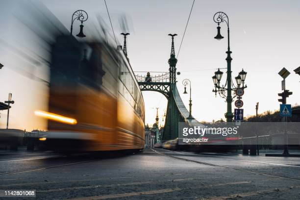 moving trams on liberty bridge, budapest - hungary stock pictures, royalty-free photos & images