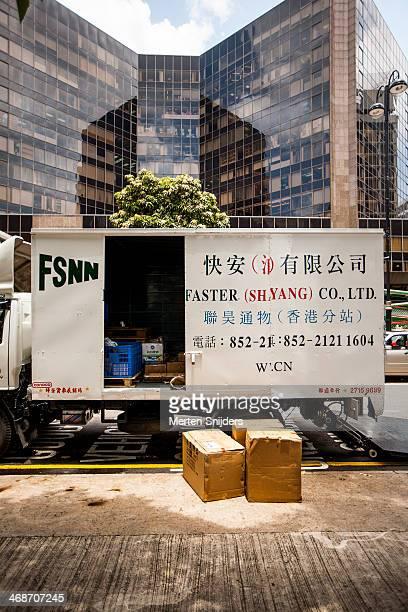 moving truck offloading boxes in city - merten snijders stockfoto's en -beelden