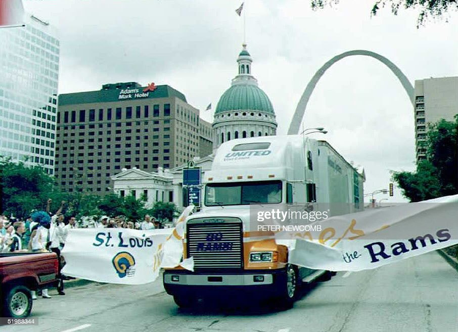 A moving van, part of a convoy of trucks carrying the equipment of the newly transplanted St. Louis Rams football team, breaks through a welcoming banner as the trucks arrive in St. Louis 26 June after their trip from the team's former Los Angeles home. The move of the Rams leaves Los Angeles with only one team, the Los Angeles Raiders, and they are intending to move back to their former home in Oakland, California.