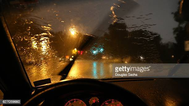 moving windshield wiper view of a moving vehicle - windshield wiper stock photos and pictures