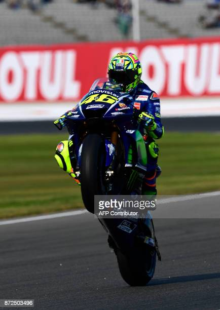 Movistar Yamaha MotoGP's Italian rider Valentino Rossi makes a wheelie during the second MotoGP free practice session of the Valencia Grand Prix at...