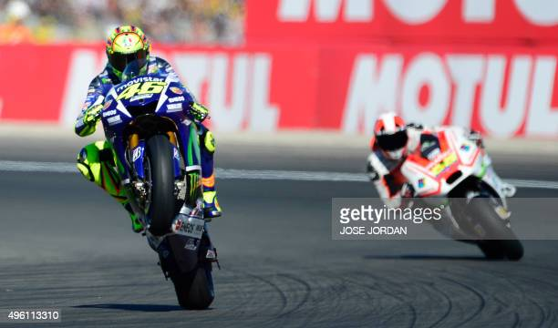 Movistar Yamaha MotoGP's Italian rider Valentino Rossi pulls a wheelie during the MotoGP qualifying session on the eve of the Valencia Grand Prix at...