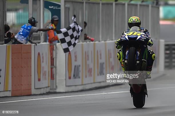 Movistar Yamaha MotoGP's Italian rider Valentino Rossi pulls a wheelie after finishing second in the Malaysian MotoGP at the Sepang International...