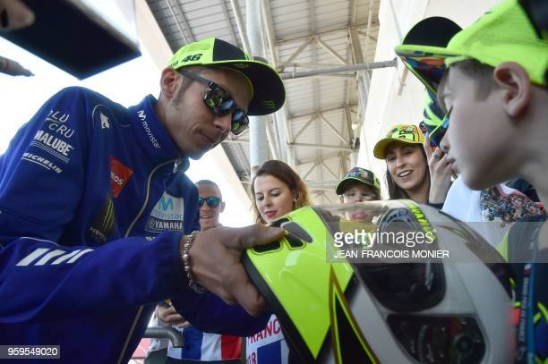 Movistar Yamaha MotoGP's Italian rider Valentino Rossi signs autographs for young fans following a press conference before a motoGP free practice...