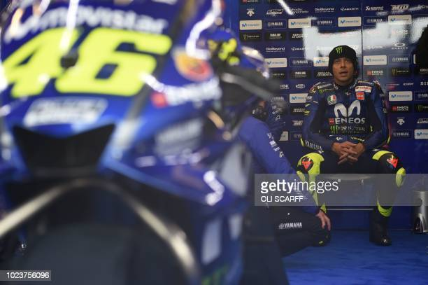 Movistar Yamaha MotoGP's Italian rider Valentino Rossi sits as the start of the MotoGP race is delayed due to rain during the motorcycling British...