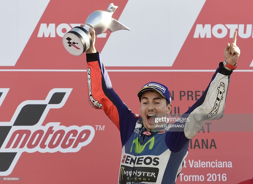 Movistar Yamaha MotoGP's Spanish rider Jorge Lorenzo celebrates winning on the podium after the MotoGP race of the Motul Comunidad Valenciana Grand Prix at the Ricardo Tormo racetrack in Cheste, on November 13, 2016. / AFP / JAVIER