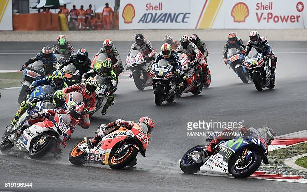 Movistar Yamaha MotoGP's Spanish rider Jorge Lorenzo leads Repsol Honda Team's Spanish rider Marc Marquez and the rest of the pack at the start of...