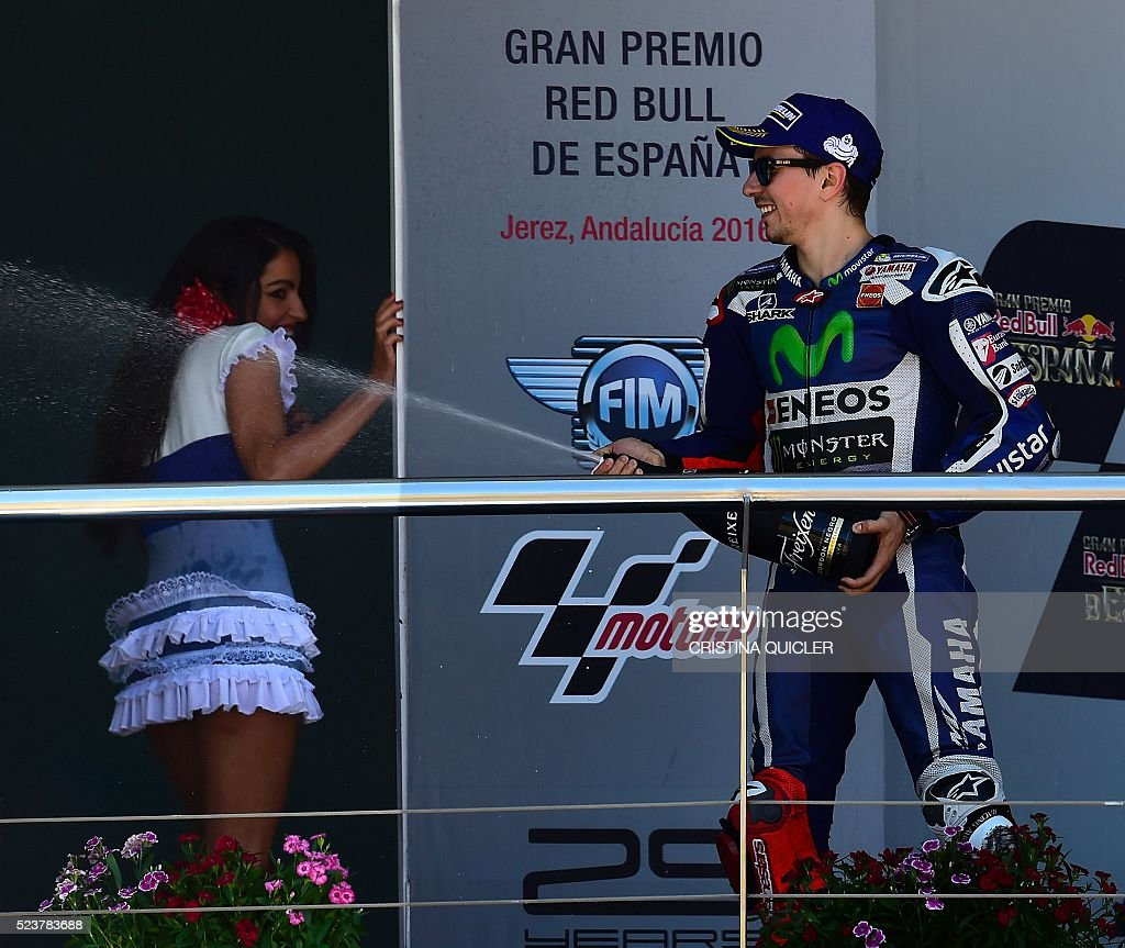 Movistar Yamaha MotoGP's Spanish rider Jorge Lorenzo (R) sprays cava as he celebrates his victory on the podium of the MotoGP race of the Spanish Moto Grand Prix at the Jerez racetrack in Jerez de la Frontera on April 24, 2016. / AFP / CRISTINA