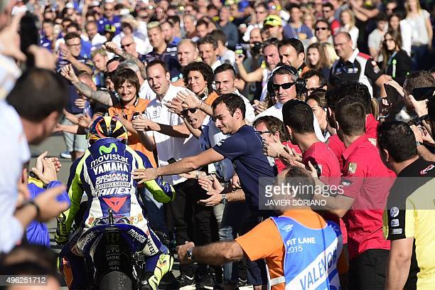 Movistar Yamaha's Italian rider Valentino Rossi is congratulated by speactators on arrival to his pit garage after the MotoGP motorcycling race at...