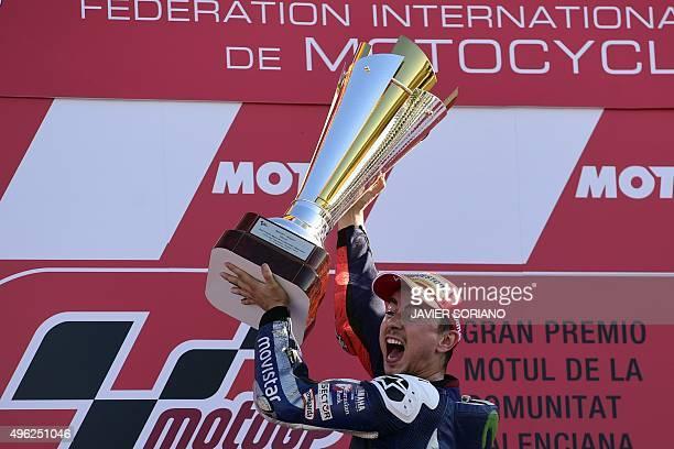 Movistar Yamaha's Spanish rider Jorge Lorenzo celebrates on podium winning the race and the 2015 MotoGP world championship tiltle after the MotoGP...