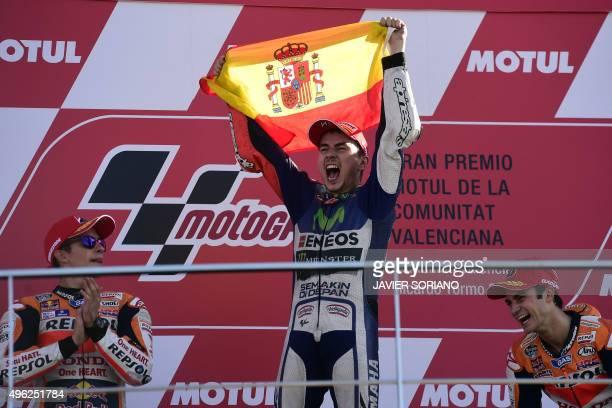 Movistar Yamaha's Spanish rider Jorge Lorenzo celebrates on podium winning the race and the 2015 MotoGP world championship tiltle with Repsol Honda's...