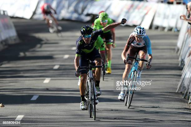 CORRECTION Movistar's Spanish rider Alejandro Valverde celebrates as he crosses first the finish line followed by AGR2R La Mondiale's French cyclist...