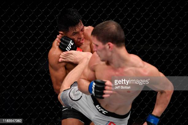 Movsar Evloev of Russia kicks Enrique Barzola of Peru in their featherweight bout during the UFC Fight Night event at Singapore Indoor Stadium on...
