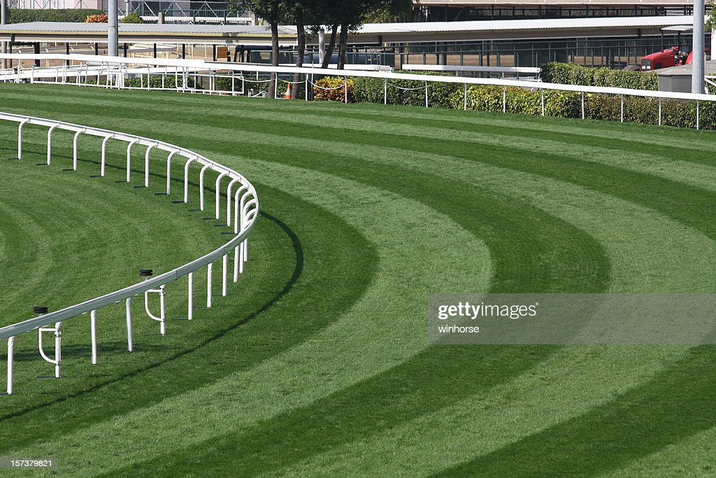 Mowed lawn used as a horse racing track restricted by fence : Stock Photo