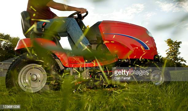 mower with flying grass clippings - lawn mower stock pictures, royalty-free photos & images